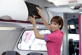 Flugbegleiterin beim Verstauen von Gepäck